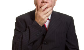 Surprised senior covering mouth with hand by Shutterstock