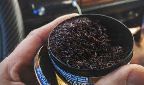 tin full of chewing tobacco, held in the hand of a man sitting behind the driver's wheel inside a car