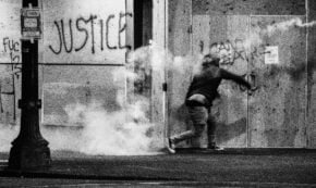 Grayscale photo of man at protest throwing tear gas cannister back at police