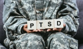 military member in fatigues holding block letters of P T S D