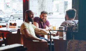 3 men sitting at a cafe table indoors laughing